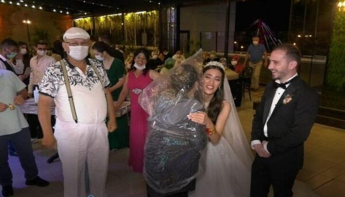Düğünde görülmemiş koronavirüs önlemi! Kafasına poşet geçirip gelin ve damada sarıldı